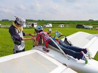 かっこいい操縦も「そこじゃなくて股からベルト通して」など補助とのどろくさい装着作業がある