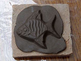 粘土を取り出し、カタの裏側に乗せる。当時の粘土は石ころとか入っていて、もっと泥っぽかった。