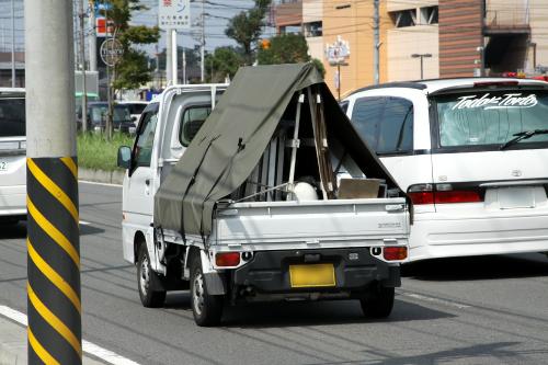 テント状に防水シートを張るなど、荷積みの工夫がうかがえる軽トラ