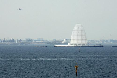 同じく人工島である「風の塔」越しに見る川崎。対岸は遠い