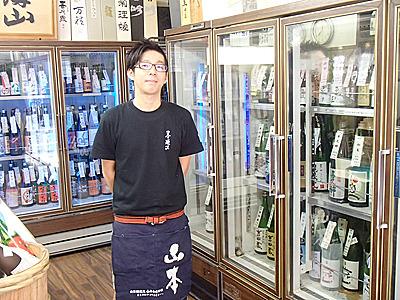 新井屋酒店の田中さん。良い日本酒が各種揃っています。