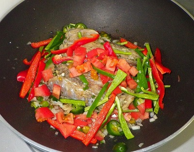 タマネギとトマトを底に敷いた鍋に移し、ピーマンなどを加えて火にかける。