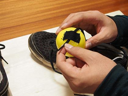 接着したナイロンベルトに靴紐を差し込む。