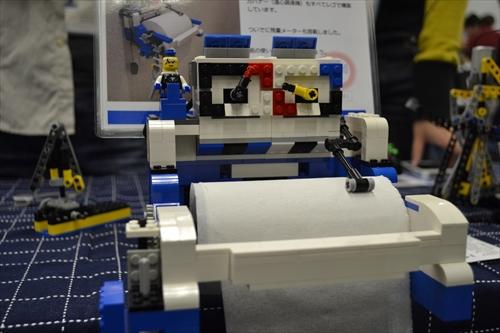 Kohsuke's Lab.によるタコメーターつきトイレットペーパー。トイレットペーパーを引っ張ると上部のメーターがググーッと動く。
