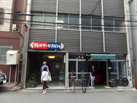 赤青鉛筆が目印の自社ビル。一階にはおしゃれな自転車屋さんが入っている