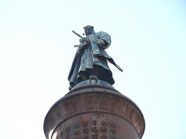 かなり高い銅像。下から見上げると、しかし、参道真正面ではなくやや左方向に身体をひねっていらっしゃる。