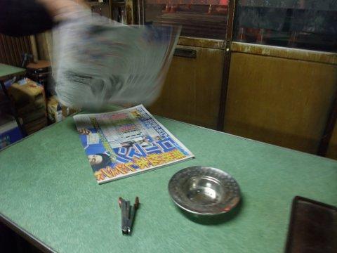 テキパキと新聞をホッチキスで綴じる
