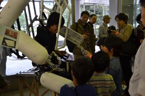 子供と握手する外骨格ロボット