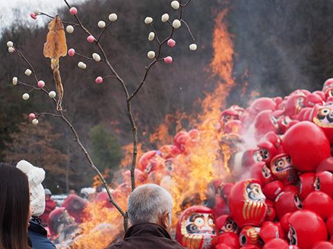 だるまを燃やした火で餅とスルメを焼くおじいさん。いかにもどんど焼きな風景。