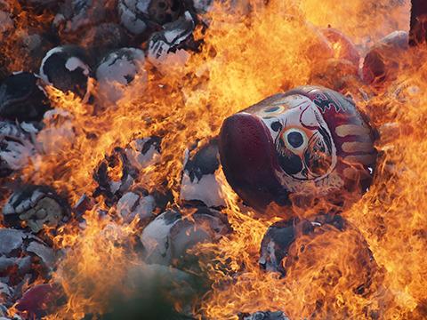 燃えながら、山から転がり落ちるだるま。