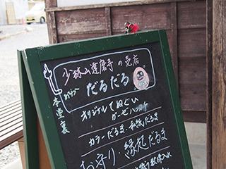 お寺の売店看板にもかわいいだるまの絵が。「だるだる」という店名もいい。