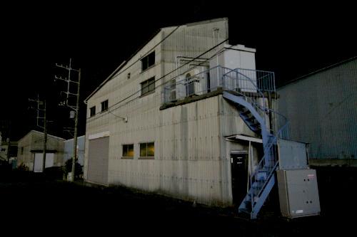 街灯が少なく、薄暗い中にトタンの建物が浮かび上がる