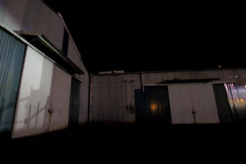近隣商業施設のネオンや、車のライトがトタンに表情を与えるようだ