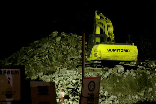 寒空の下、瓦礫の山に停められたシャベルカー