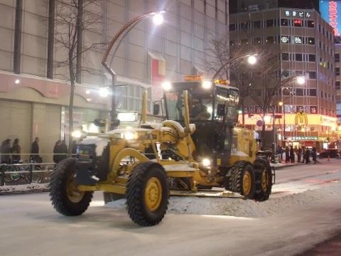 除雪グレーダ(というらしい)でガリガリと圧雪を削り取る
