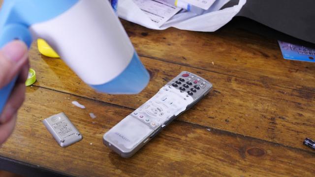 電池を抜いたリモコンにのりを塗って乾かす。水のり、ボンド厚め、ボンドうすめ、ボンドを水でうすめたもの、の4層にわけてテストをした