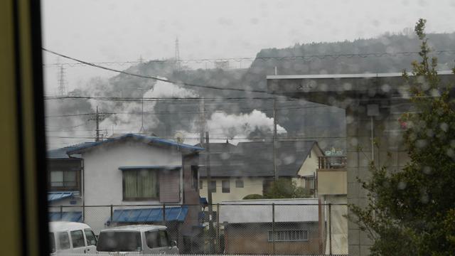 電車の車窓から。いたるところで煙が上がってる街、富士市