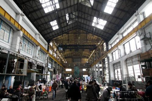 どどんと広がる工場の中、展示パネルや出店が並ぶ