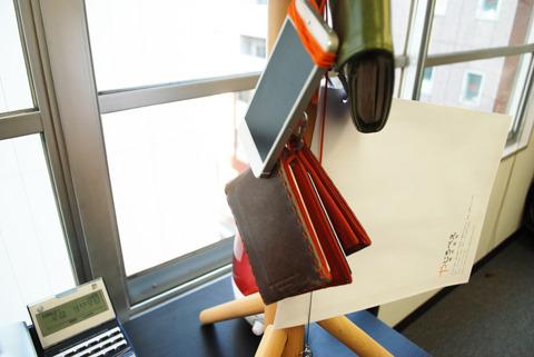 スマホ、手帳、鍵、財布、仕事で使う書類を入れる封筒など、大事なものをヒモでつないでおく