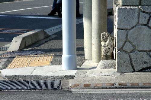 道路の反対側、電柱の根元にポツンと小さな石があった