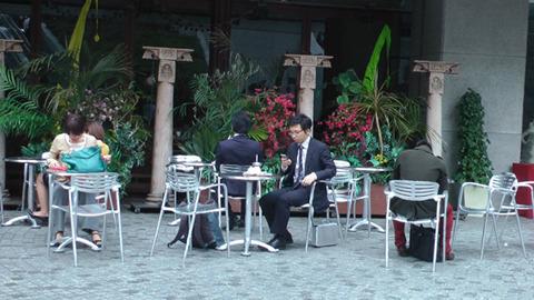 テラス席にいるスーツ姿の男、足元にはアタッシュケース