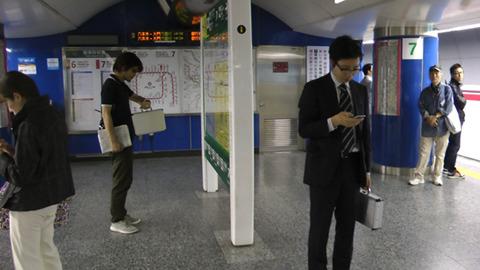 次の指令は駅のエスカレーター。予定時刻までエスカレーター前で待つスパイが二人。大きな矛盾を感じる。
