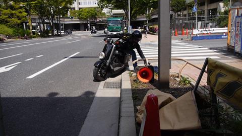 植え込みに落ちたカバンをバイクが拾って去っていく