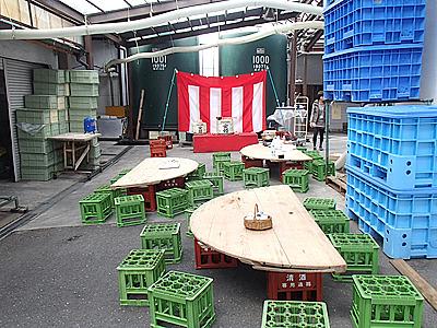 蔵の一画。屋根のある場所を借りての開催。テーブルは窯のフタ。イスは酒瓶のケースです。蔵ならではの設備。
