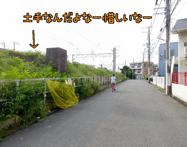 向こうのほうで建物に阻まれて道が線路から離れて右に曲がっている。でもなー、線路が土手なんだよなー。