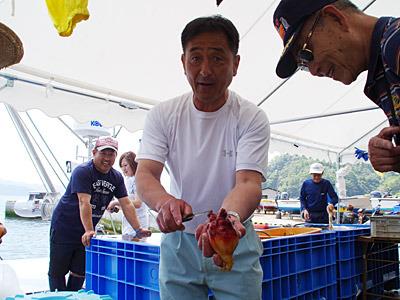 ホヤの食べ方を教える漁師さん。水管のマイナス側から切るんですよね!