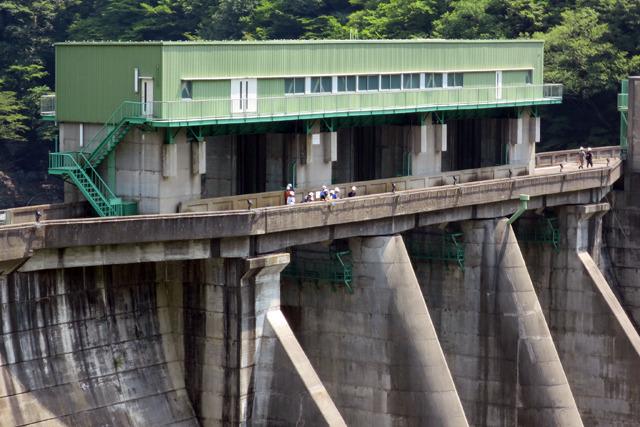 ダムの上にヘルメットをかぶった集団が見えた