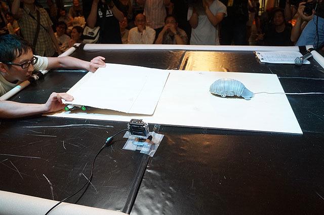写真左。平たいボディを床と一体化させ相手の下にもぐりこみ、転ばせる作戦