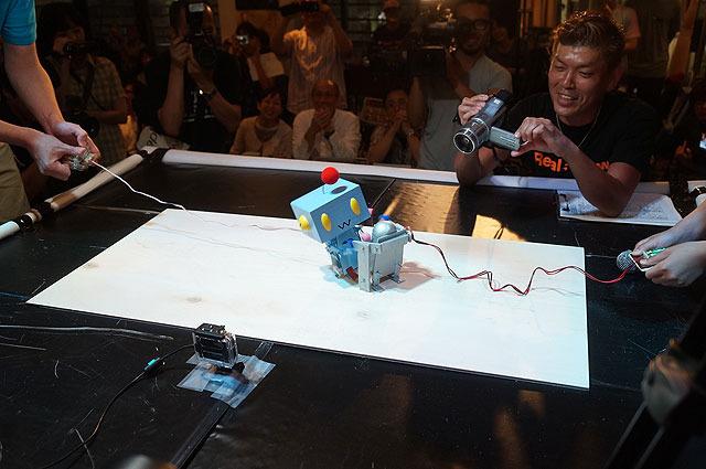 お互いバランスを崩しながらどんどん接近していく2体のロボ。そのとき、体勢を崩しかけたクーちゃん零号機の足元をTsukubot3号がすくった!!