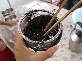 茶漉しに入れた黒作りを水で洗い、黒い液体を作成。