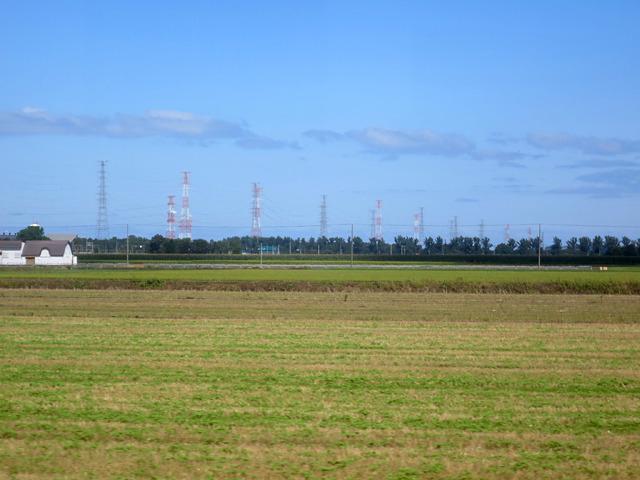 人家がほとんどなくなり、広大な農地の先に鉄塔の列