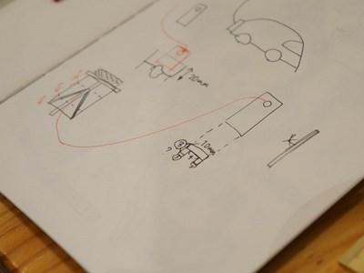 切り出した板にヒモを通して凧をくくりつける、という図。