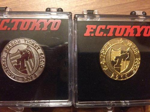 FC東京では年間チケット購入者を「ソシオ」と呼ぶそうで、Kさんはそれを10年続けた「10年ソシオ」なのだそうだ。10年目にもらえる金バッジも持っている(右)