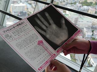 こちらパソコンで手をスキャンして紙が手渡されるコンピューター手相占い。占いに徹底的な効率化が導入された。