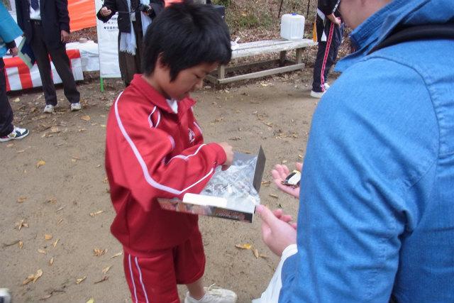 綱引き参加者にお菓子を配る小学生に大人が群がる