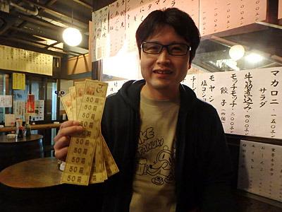 まず2千円分のチケットを購入した先輩。なぜか通販で幸運のネックレスを買った成功者みたいな写真になった。