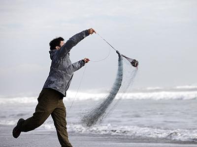 潮が引いたタイミングで走り込んで、素早く網を投げ込む。
