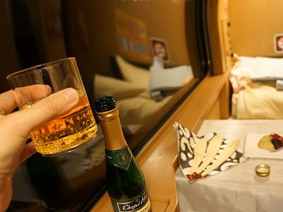 スクリューキャップのシャンパンを開ける。寝具にカンパーイ。