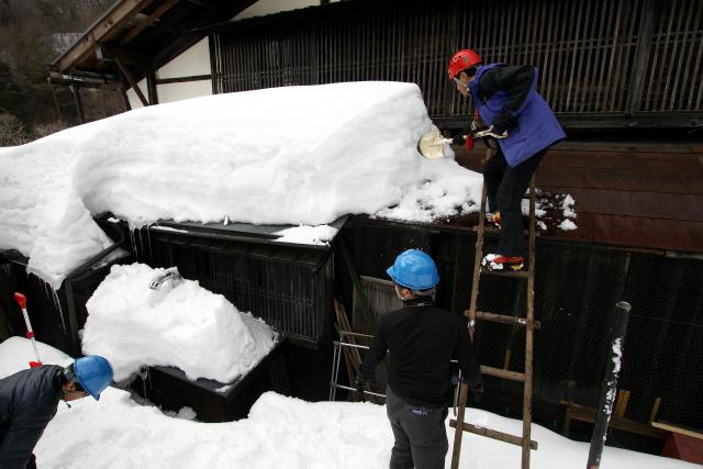 庇にハシゴを掛けて、スコップで雪を下ろす