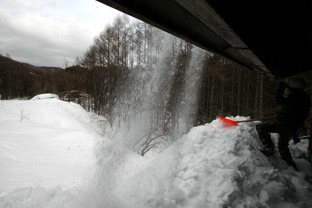 二階の庇から降り注ぐ雪煙を眺めつつ、私もまた雪を掘る