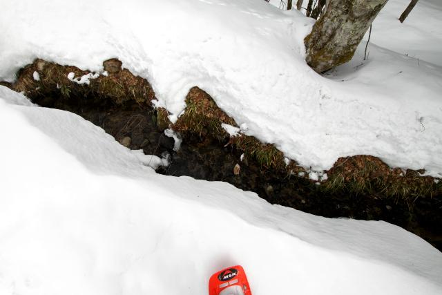 屈めば水が汲めた用水路も、雪が積もると手の届かない高さになる