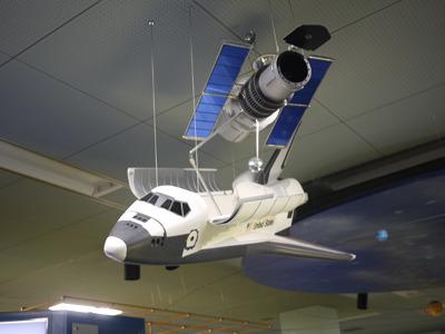 こちらは天井に吊られており納得感のある人工衛星(こちらの記事より)</a>