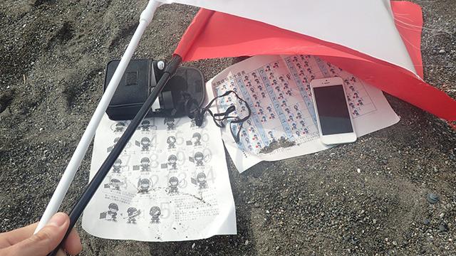 今回の実験の持ち物。旗振り用の旗、手旗信号のテキスト、双眼鏡、スマホ。