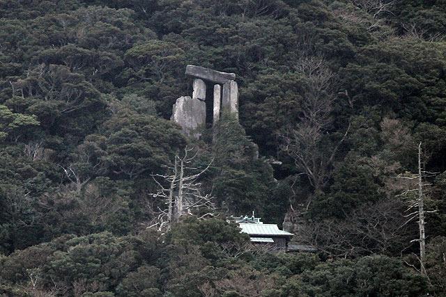 遠くから望遠で見た王位石。巨大な石が鳥居のカタチに組んである。その下に見えるのは神社。沖ノ神島神社という。