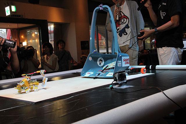 過去もっとも巨大だったロボット、チリトリーマアム。(写真奥) ラジコンに乗せたチリトリで相手をすくい上げて転ばせる/押し出す作戦だったが、4体バトルロイヤルで敵機ごと場外に出てしまい、残りの2機に勝ちを譲る