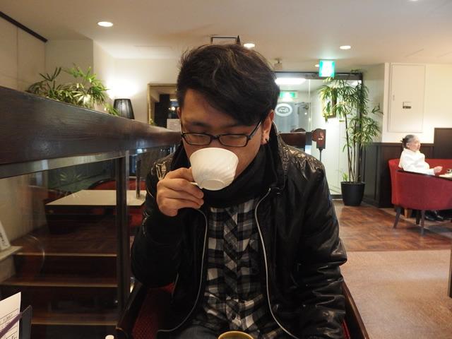 インタビュー中、コーヒーを飲むシーブックさん
